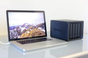 Synology-NAS neben MacBook Pro auf dem Schreibtisch